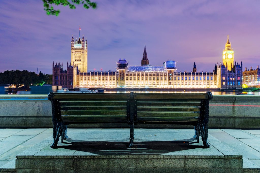Bench at night with Houses of Parliament in the distance