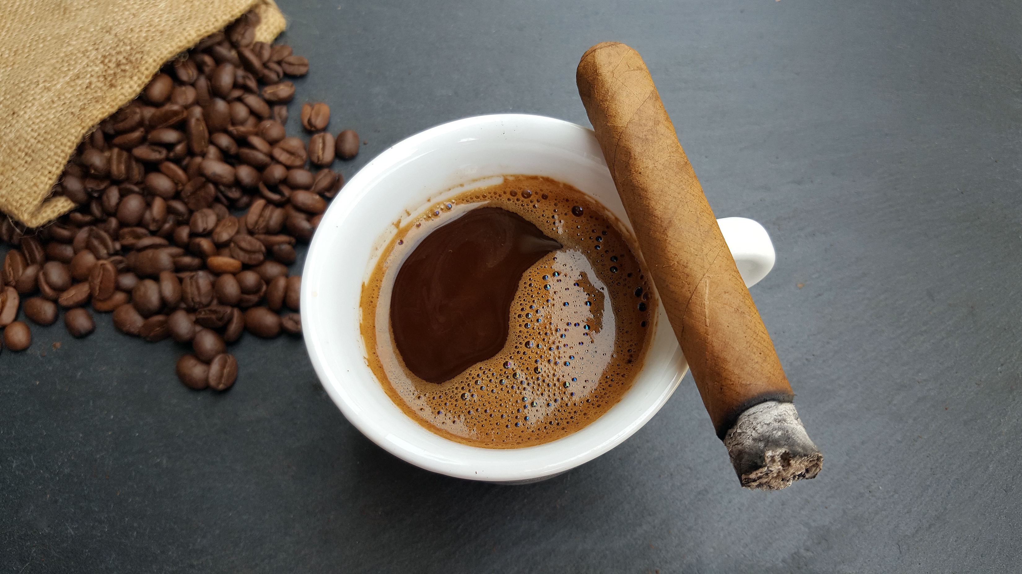 Coffee cup, beans and cigar on dark stone background